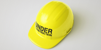 """Yellow hard hat with words """"Under Construction"""" on it"""
