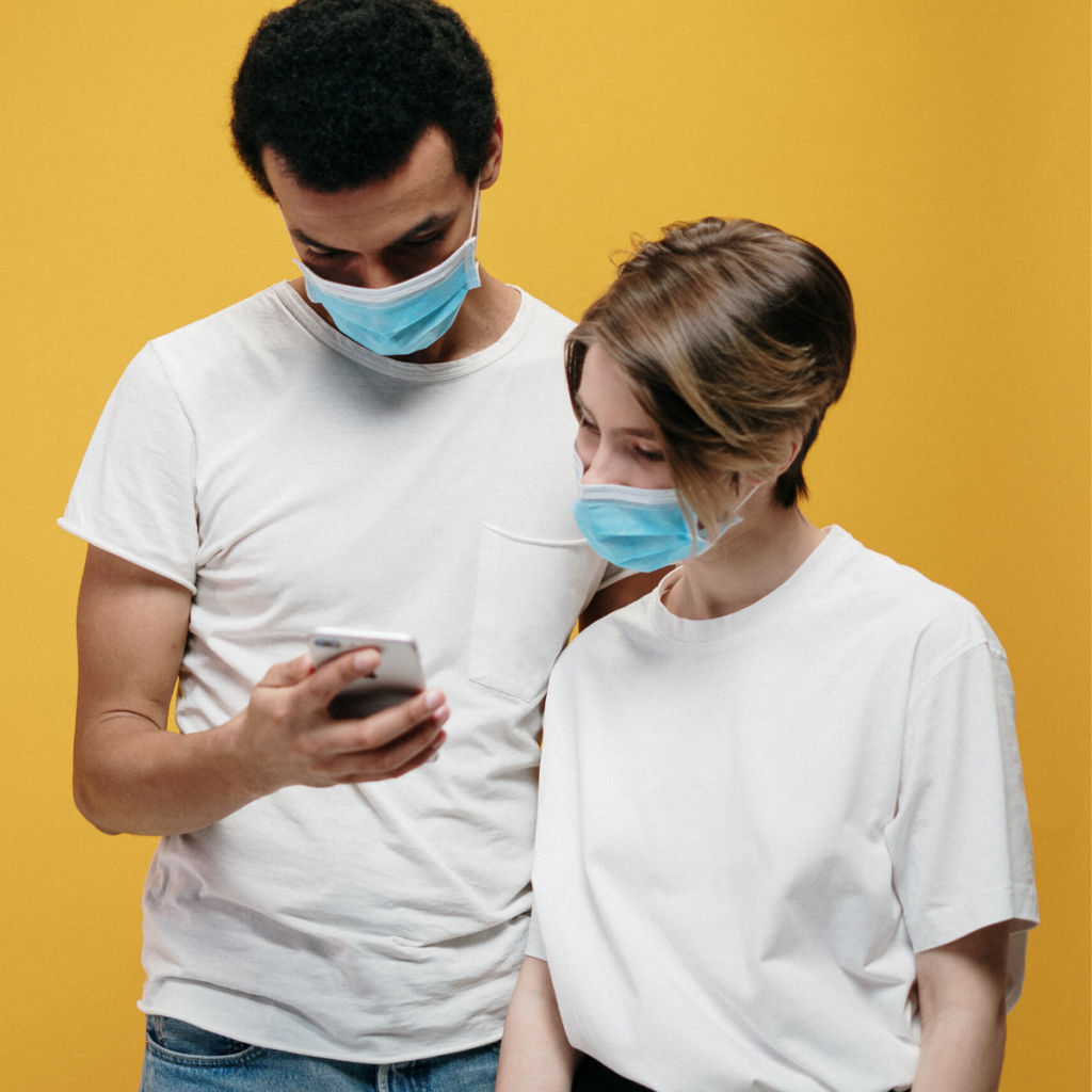 Two young people wearing masks looking at a cell phone